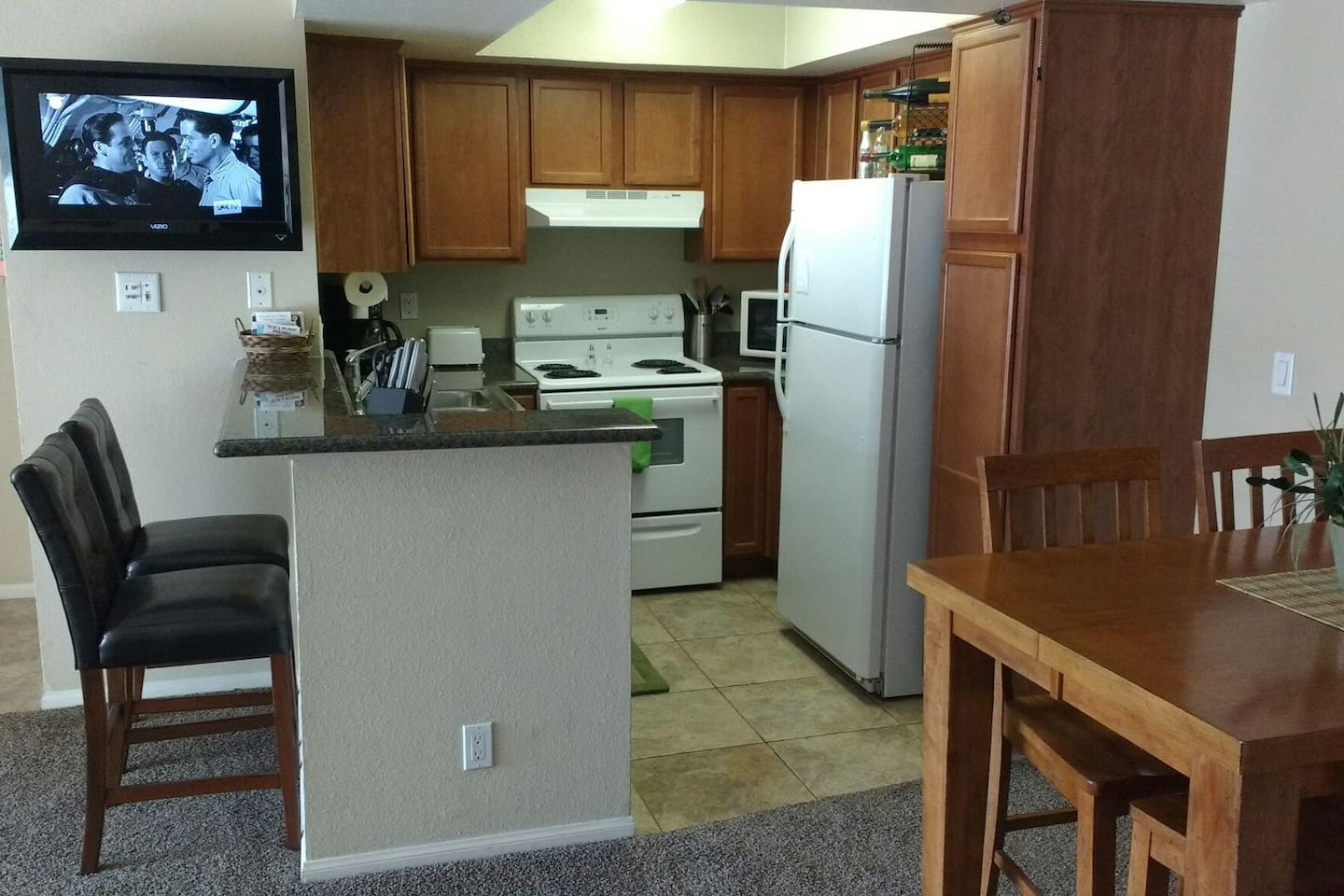 kitchen with a bar and 2 stools