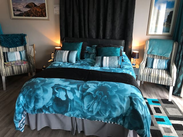 The refurbished bedroom area in the open plan studio apartment with a very comfortable double bed, comfy armchairs to relax in & look out at the coastal & mountain views from the French doors.