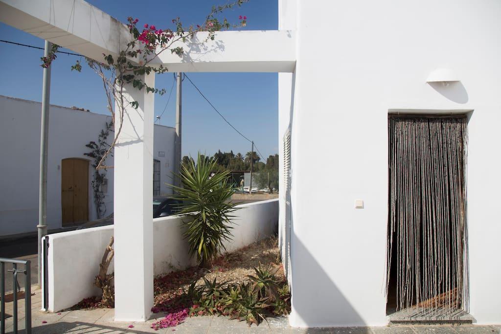 Acceso exterior a la vivienda, con la verja a la izquierda y la puerta de la casa a la derecha.