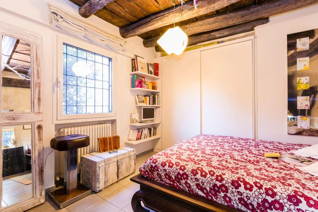 La camera da letto dai toni caldi con letto orientale a doghe in legno e materasso memory