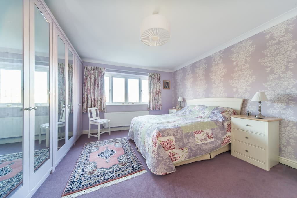 Saffron double bedroom with King size bed, mirror wardrobes and calm decor.