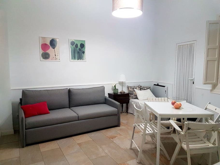 Salón comedor de altos techos con smartTV, camita auxiliar y sofá cama de 1.40