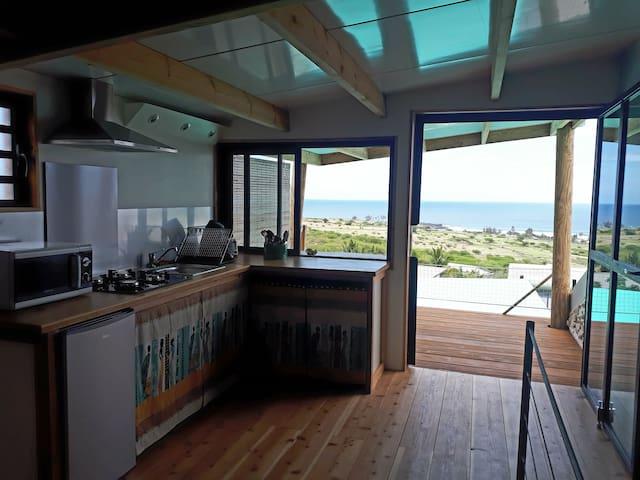 Cuisine donnant sur la terrasse couverte ; vue sur la savane et l'océan indien