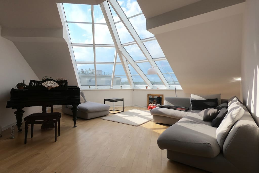 The living room with a large and comfy corner sofa, a grand piano and a huge corner skylight.