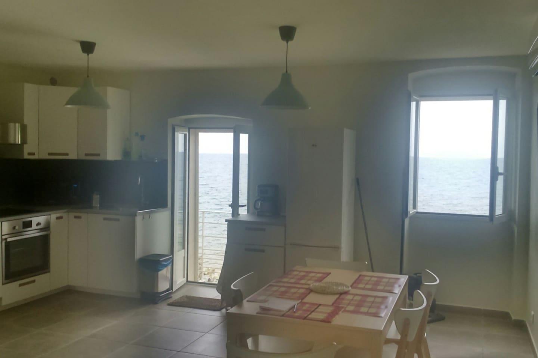 salon avec cuisine américaine et terrasse