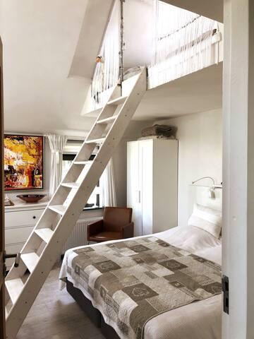 De trap staat een beetje in de weg, maar draagt ook bij aan de fijne sfeer. Je kunt dus beneden slapen in een heerlijke boxspring,  maar ook romantisch met z'n tweeën boven.