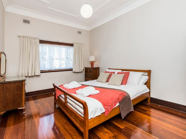 Spacious bedroom with high ceilings and comfy queen size bed