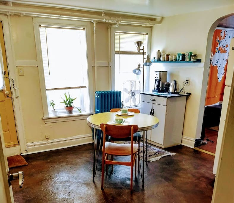 Mid-century modern kitchen, fully stocked coffee bar, with view into living room.