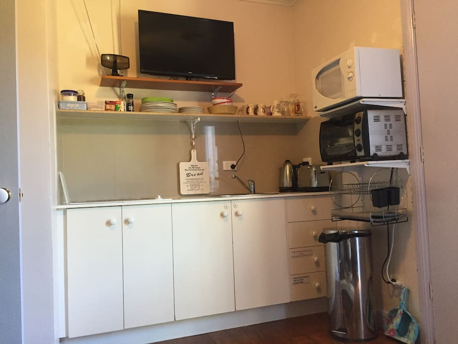 Fully equipped kitchen with sink, 4 burner cooktop, convection oven, microwave, fridge, toaster, jug, utensils and anything else that you would require. The TV is on the wall above which is opposite the lounge chairs.