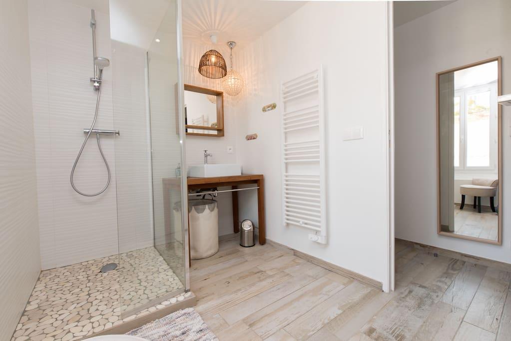 À côté de la chambre on trouve une Salle d'eau claire, avec sa douche à l'italienne en galets - douchette écologique . Elle comprend une fenêtre et des toilettes séparées.