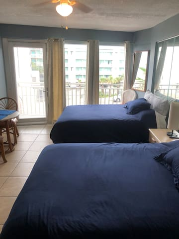 Open space, tiled floor, and two queen size beds with new navy blue bedding, pillow tops, and memory foam pillows.