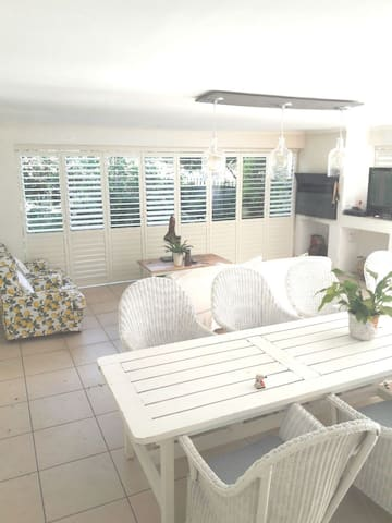 Our beautiful patio with 10 seater dining table as well as lounge with DSTV. All the american shutters stack back and the patio opens up onto the front garden.