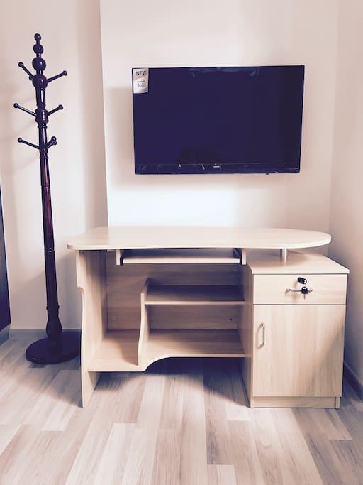 A smart TV, desk and chair.  一台智能电视,书桌和椅子。