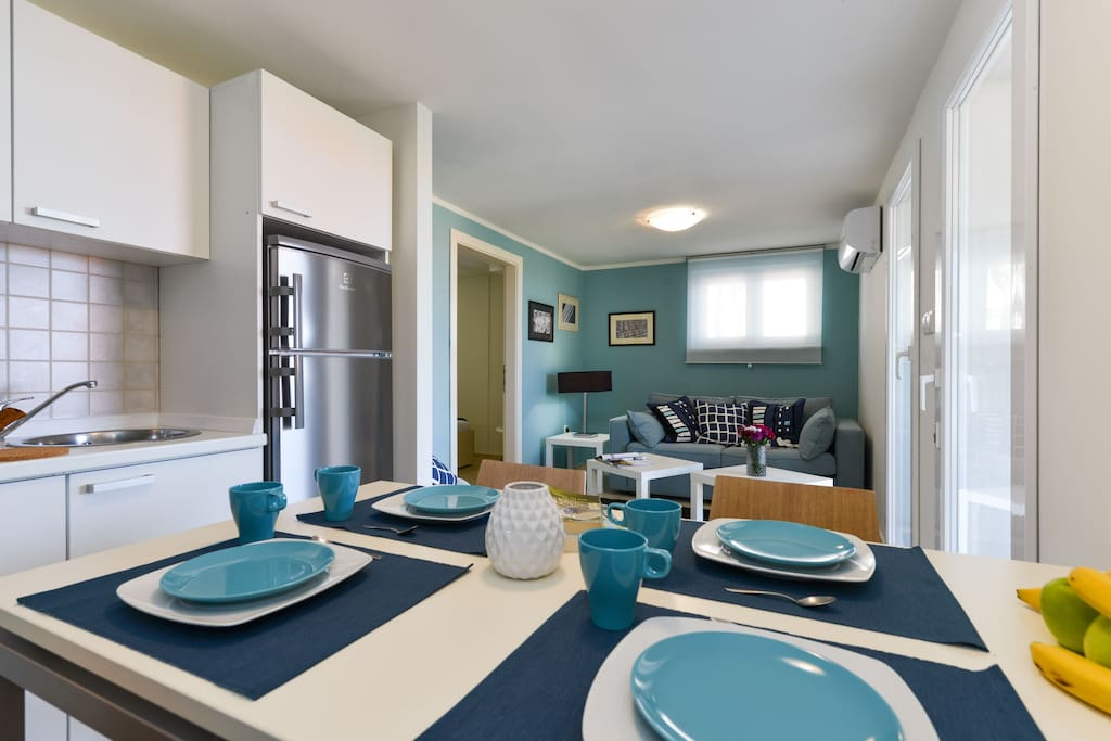 Dining table, kitchen and living room with two-seat sofa-bed