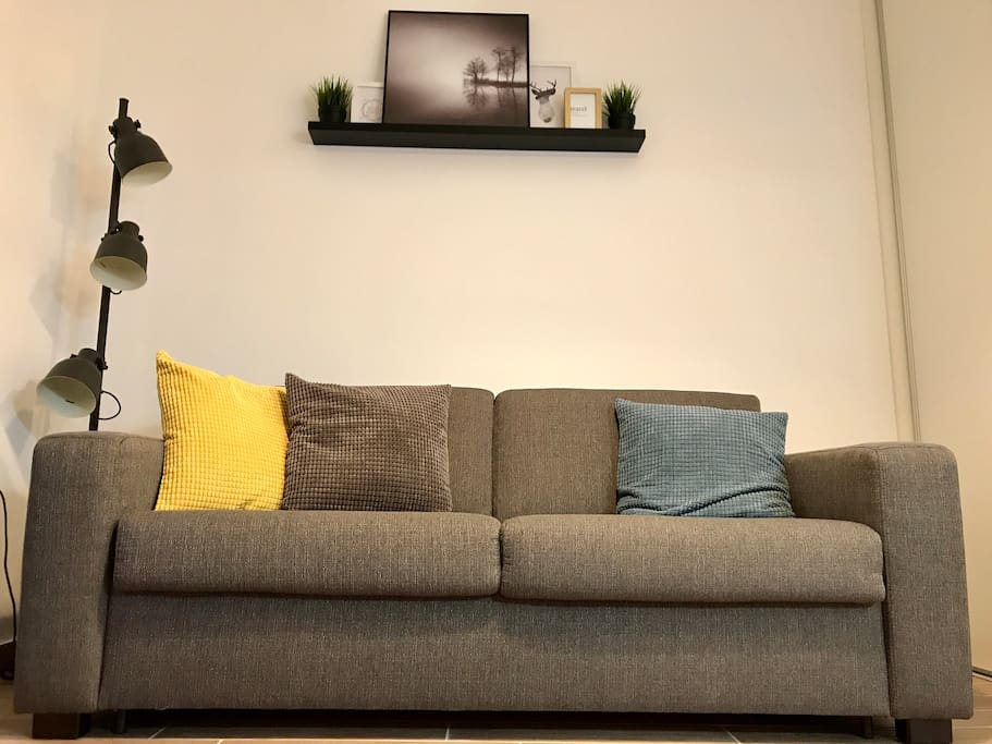 Living room with carefully chosen details like industrial lamp, soft and colorful pillows and modern photography