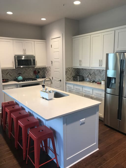 A bright white kitchen with quartz countertops and stainless appliances.