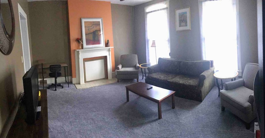 View of living room. Small desk area. Cable TV and WiFi. The sofa is a sleeper and an air mattress is available.