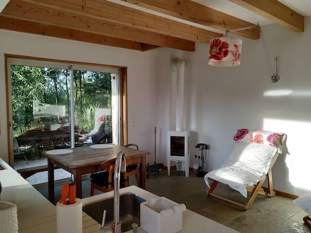 La pièce à vivre, grande baie vitrée, poêle à bois.
