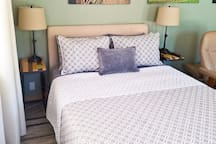 Queen size bed with two side tables with USB port and power strips.