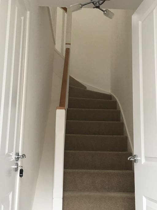 Entrance with integral garage access and stairs leading to the upstairs apartment.