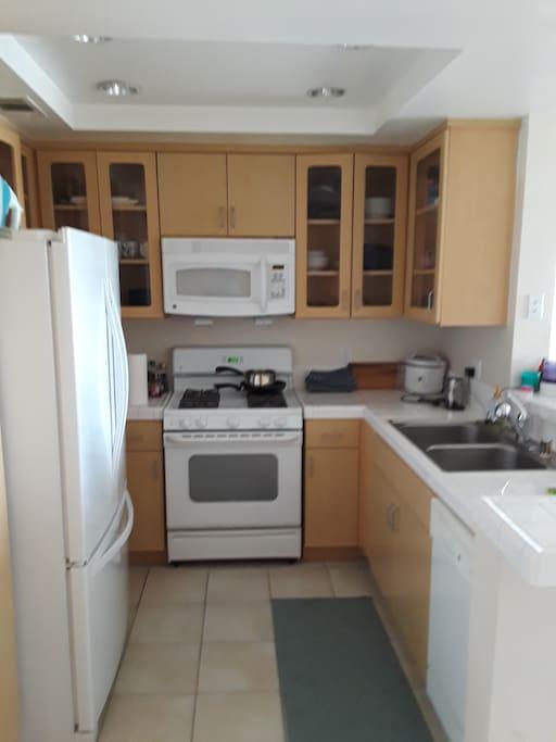 Kitchen with fridge, microwave, oven, washing machine, Nespresso machine