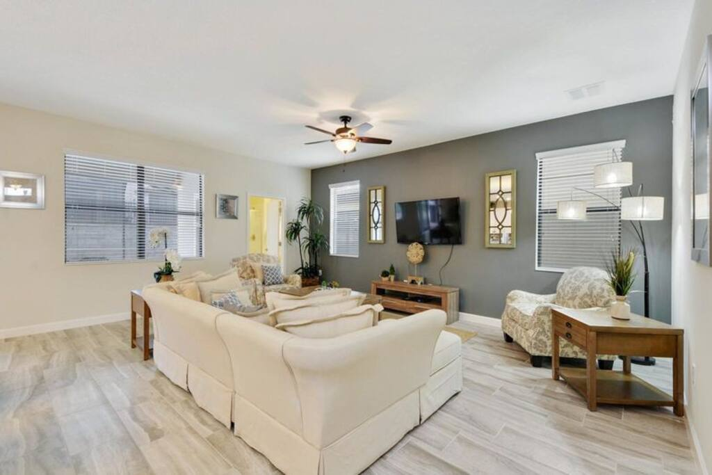 The retreat at championsgate villa's beautiful furnished living room with big flat screen TV