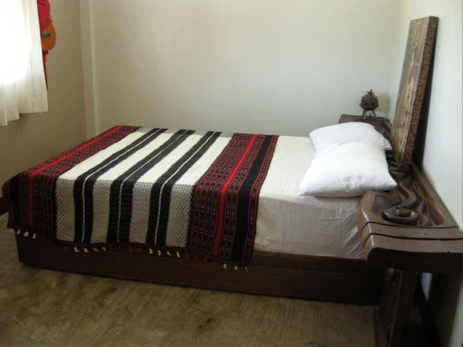 The room is equiped with a double bed, topped with a wooden headboard.