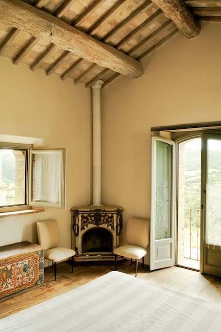 detail of the bedroom A,ancient fireplace and window overlooking the valley