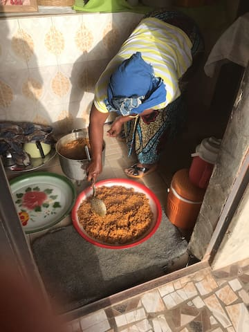 Mama Aminata cooking her famous 'Benachin with chicken'.
