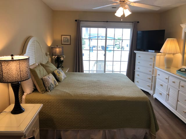 King size mater bedroom with access to back balcony and private bathroom