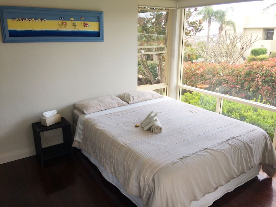 Large double bedroom with queen bed and  robe captures lots of sunlight.