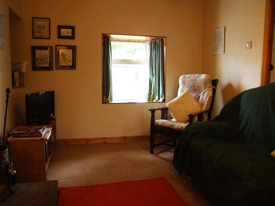 The sitting room has a two seater sofa, armchair and rocking chair, with TV/DVD, games and books.