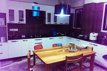 Modular kitchen and dining area equipped with induction cooker, gas stoves, rice cooker, microwave oven and fridge.