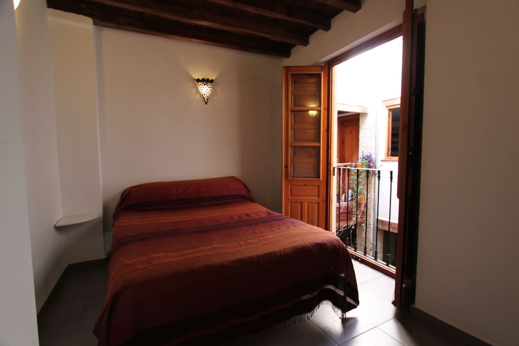 Bedroom 3 with double bed and doors opening onto internal courtyard.