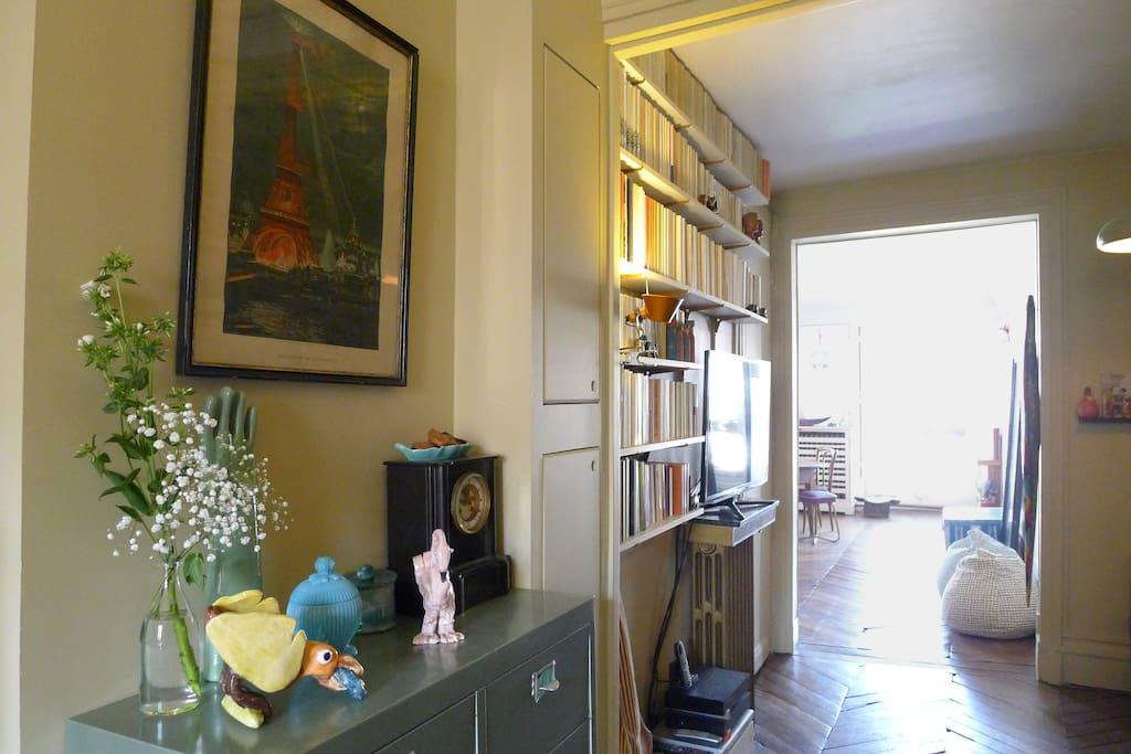 Un joli dégagement meublé habillé de livres entre la chambre, la cuisine et le salon. Dans un renfoncement à la droite de l'image se trouve le canapé convertible.