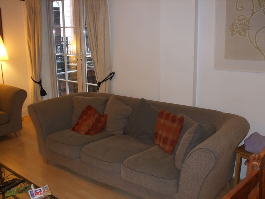 Living room.  Two large sofas.  Glazed doors onto balcony.