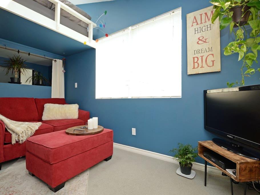 Flat Screen TV to watch in your cozy living room below loft bed.
