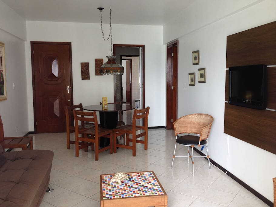 Sala com piso cerâmico, sofá cama, TV e sacada