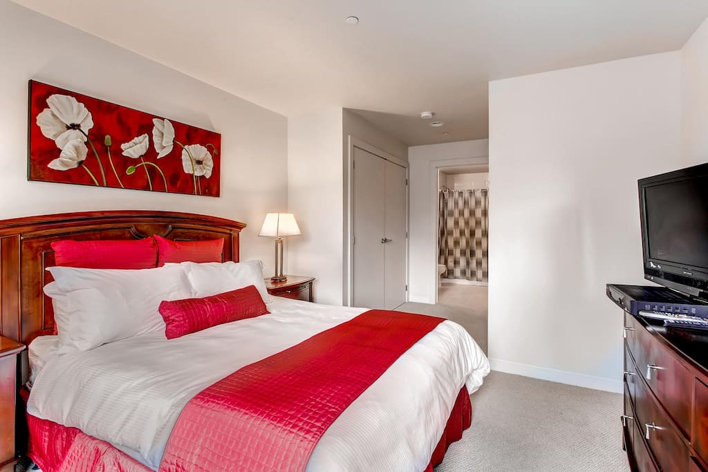 Master bedroom with dresser, flat screen TV and private bathroom