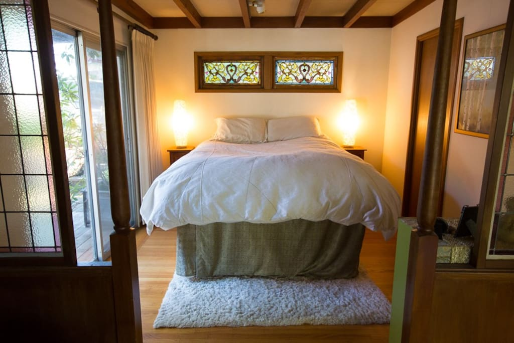 Bedroom with sliding doors to the deck and stained glass windows.  There is a full size futon bed under this queen platform that can be pulled out and put on the floor to accommodate another person.