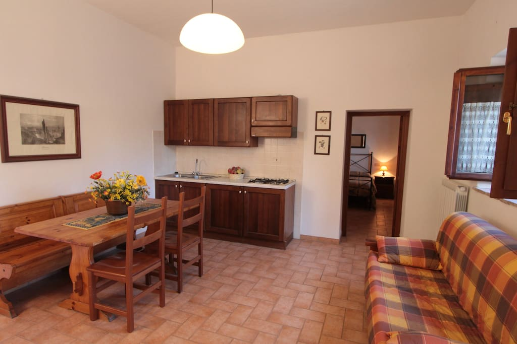 Montegonfoli Two. The large living room with the kitchenette. At the end the view of the second bedroom.