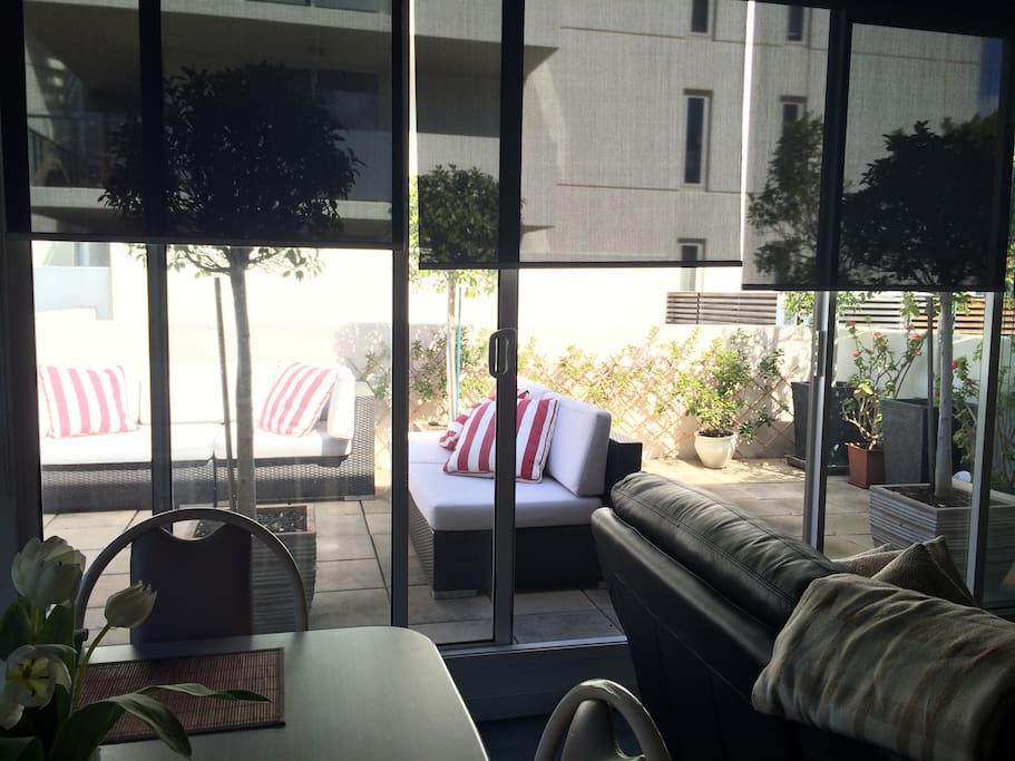 Living area opening to a large terrace with full sun in Summer