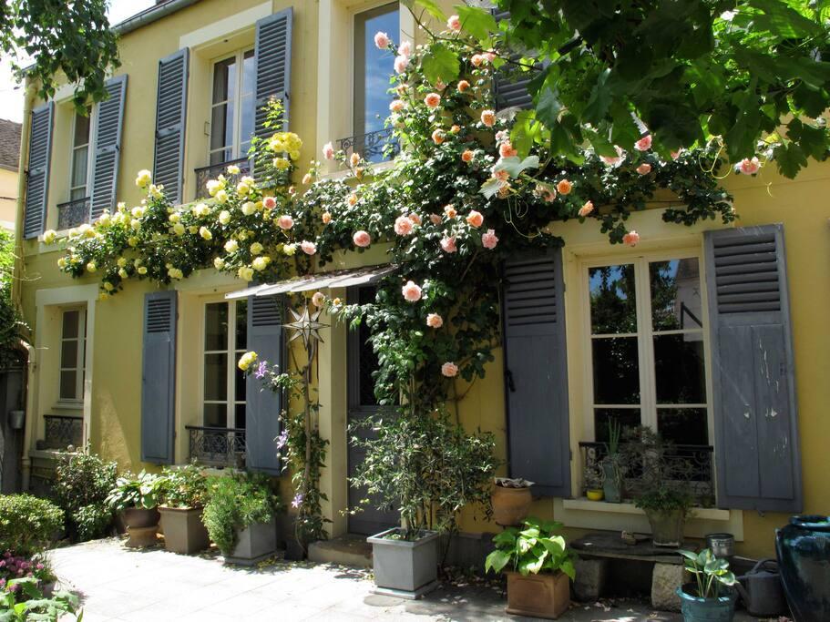 Façade fleurie dans un jardin clos et ensoleillé