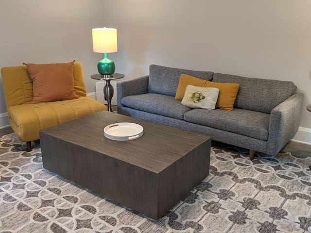 Living room features a couch and two convertable chairs that fold out into (short) twin beds.
