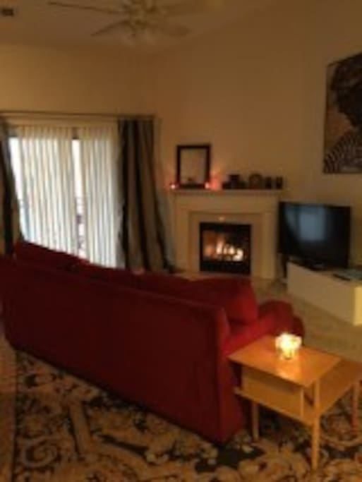 Cozy living area features gas fireplace, TV, and a couch big enough to double as a sleeping space.
