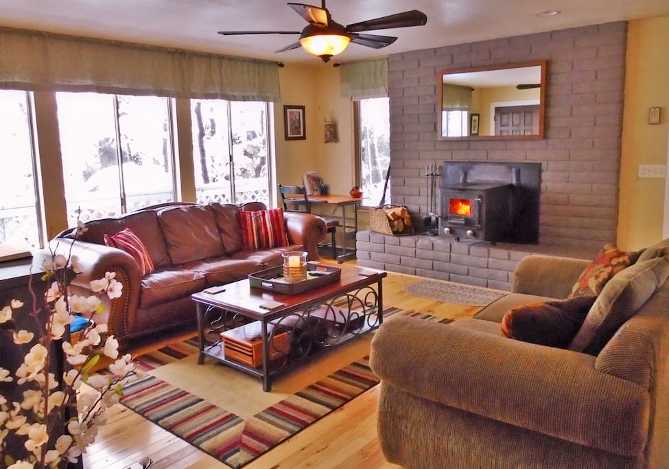 Cozy living room with woodstove.  Large windows to keep you feeling close to nature.