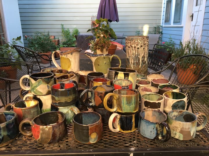 table full of mugs fresh out the kiln