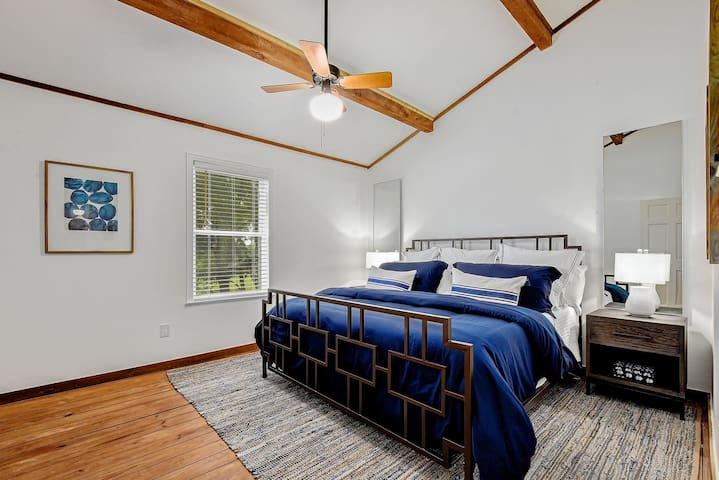"""This king size iron bed, 60"""" bedside mirrors, and oversized woven denim and natural fiber area rug perfectly blends a more contemporary feel with the rustic elements of the home."""