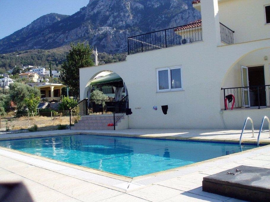 The villa and its private 8m pool with mountainous backdrop of Karsiyaka village and authentic mosque.  The kitchen (breakfast) patio is to the right.