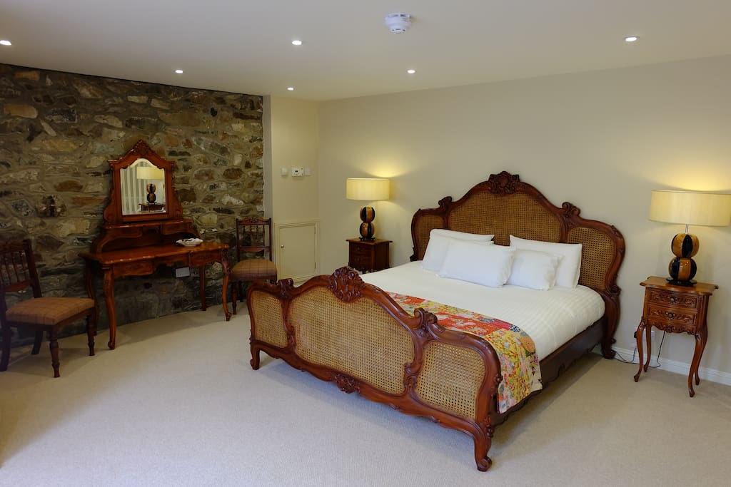 Super king bed in large room with sitting area, tv, and tea/coffee facility.